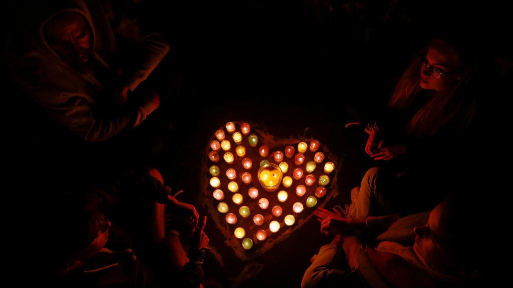 Las personas se sientan alrededor de velas en forma de corazón mientras presentan sus respetos en un lugar conmemorativo para las víctimas. 17 de marzo de 2019.