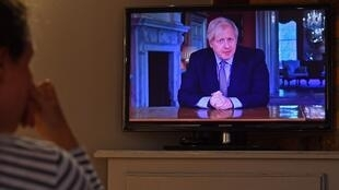 A woman watches Britain's Prime Minister Boris Johnson give a televised message to the nation in Brenchley, south east England on May 10, 2020, as the government sets out it's roadmap to ease the national lockdown due to the novel coronavirus COVID-19 pandemic.