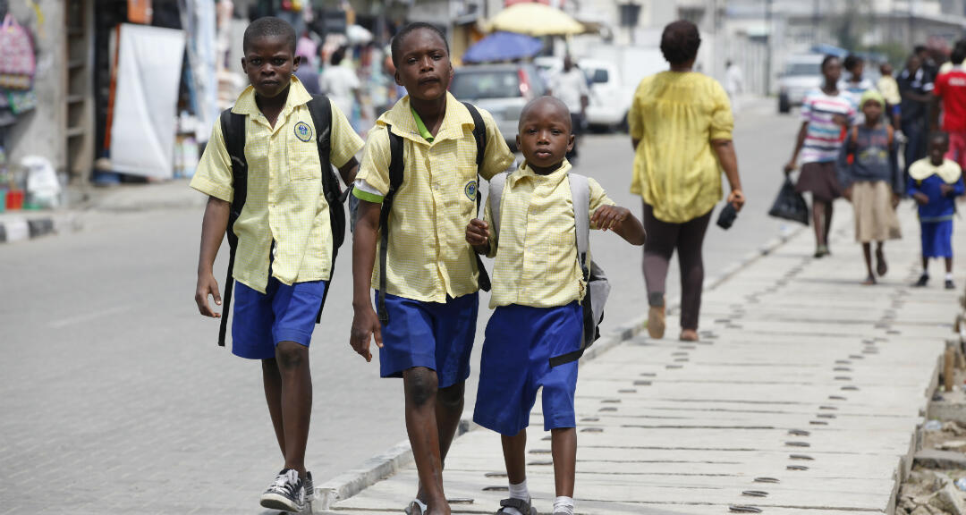 Archivo. Niños en edad escolar caminan por la calle en el área de Obalende de Lagos, Nigeria, el martes 17 de junio de 2014.