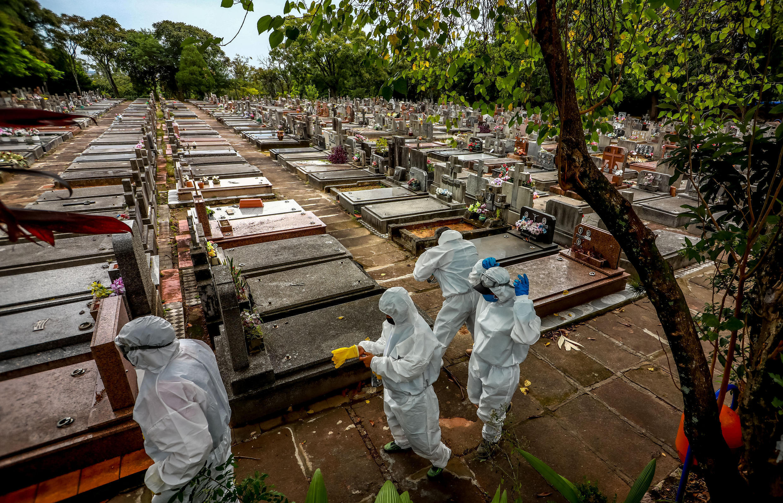 Workers prepare for the burial of a Covid-19 victim at the Sao Joao municipal cemetery in Porto Alegre, Brazil in March 2021