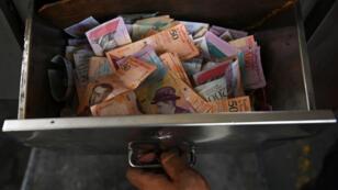 Un trabajador de PDVSA muestra una caja con producto monetario de la venta de gasolina en una estación de servicio en Caracas, el 21 de mayo de 2019.