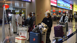 Passengers wearing face masks push luggage carts at an airport in Harbin, the capital of Heilongjiang province bordering Russia, as the spread of Covid-19 continues in China on April 11, 2020.