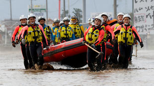 Rescue workers carry a rubber dinghy as they search a flooded area in the aftermath of Typhoon Hagibis, which caused severe floods at the Chikuma River in Nagano, Nagano Prefecture, Japan, October 14, 2019.