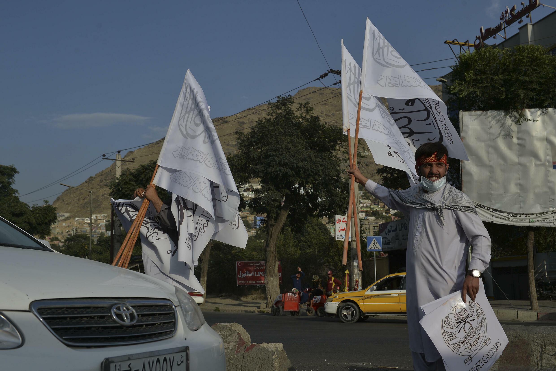 Certains vendeurs en bordure de route à Kaboul vendaient des drapeaux talibans - des banderoles blanches portant la déclaration de l'Islam et le nom officiel de leur régime.