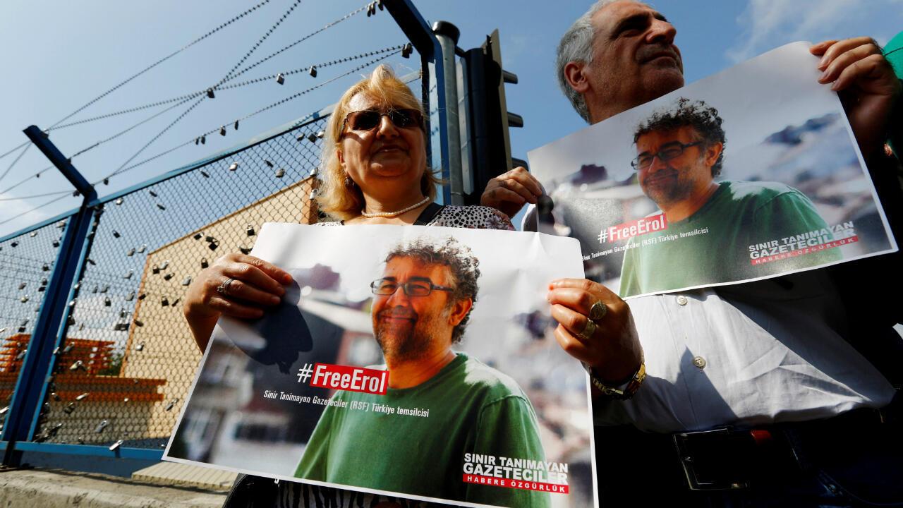 Dos manifestantes sostienen carteles con la imagen de Erol Onderoglu, uno de los tres activistas arrestados en junio de 2016. Estambul, Turquía, 24 de junio de 2016.