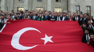 El presidente turco Recep Tayyip Erdogan posa con un grupo de sus seguidores con una bandera de Turquía frente al Parlamento en Ankara el miércoles 16 de octubre de 2019.
