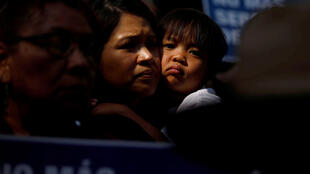 A child embraces a woman as people hold signs to protest against US President Donald Trump's executive order to detain children crossing the southern US border and separating families outside of City Hall in Los Angeles, California, U.S. June 7, 2018.