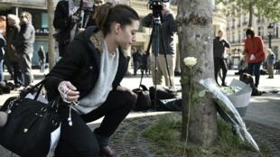 De nombreuses personnes viennent se recueillir sur les Champs-Élysées, où le policier a été abattu le 20 avril.