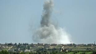 الدخان يتصاعد في أجواء قرية كفر عين إثر تعرضها للقصف في محافظة إدلب الواقعة تحت سيطرة جهاديين في الثاني من مايو/ أيار