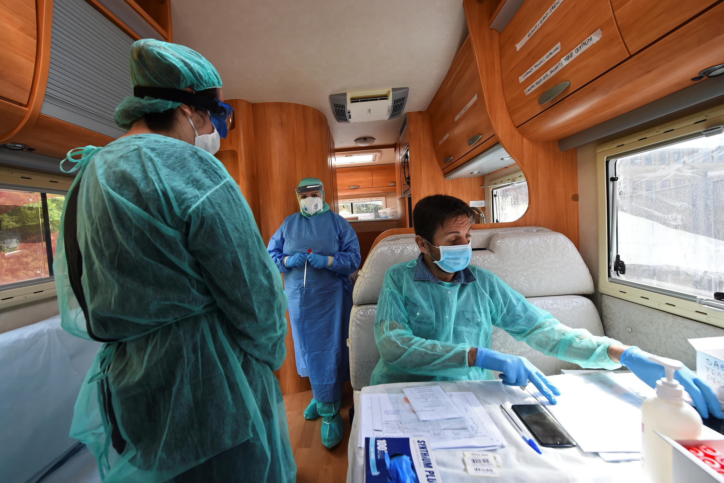 Medical workers in protective gear sit in a camper van preparing to test people nearing the end of their quarantine period in Turin, Italy, on April 16, 2020.
