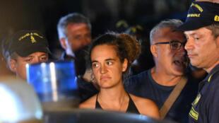Carola Rackete, capitana del barco Sea Watch 3, es escoltada por oficiales de la Policía italiana a su llegada a Lampedusa. Lampedusa, Italia. 29 de junio de 2019