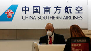 A China Southern Airlines employee wears a surgical mask as a preventive measure in light of the coronavirus outbreak in China, while he attends a customer behind the counter at Benito Juarez international airport in Mexico City, Mexico January 28, 2020.