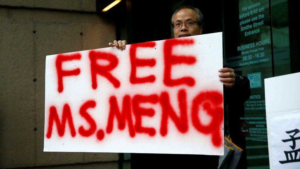 Robert Long sostiene un cartel pidiendo la liberación de Meng Wanzhou, afuera del tribunal donde se realiza la audiencia, en Canadá.