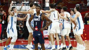 El francés Frank Ntilikina luce abatido, mientras que los jugadores de Argentina celebran, después de la segunda semifinal del Mundial de baloncesto en Beijing, China, el 13 de septiembre de 2019.