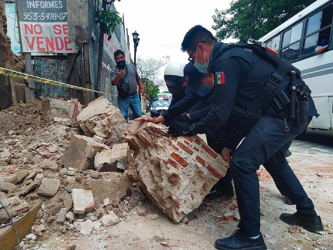 Policías y agentes de Protección Civil levantan parte de una barda derrumbada en Oaxaca, México, tras el sismo registrado el 23 de junio de 2020.