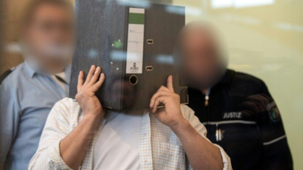 التونسي سيف الله ه. يغطي وجهه بملف في أول أيام محاكمته في دوسلدورف بغرب ألمانيا في 07 حزيران/يونيو 2019