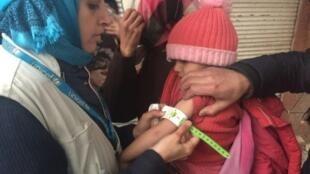 موظفة من يونيسف تعاين طفلة تعاني من سوء التغذية في مضايا، في 14 كانون الثاني/يناير 2016