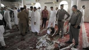 Saudi men gather around debris following a blast inside a Shiite mosque in the Gulf coastal town of Qatif on May 22, 2015.