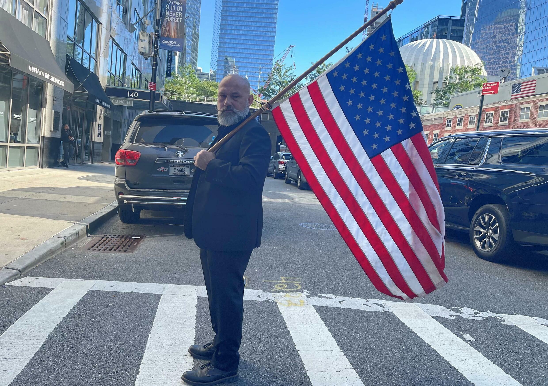 أمريكي يحمل علم بلاده قرب موقع غراوند زيرو حيث وقعت اعتداءات سبتمبر 2011