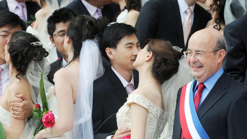 Couples de mariés chinois qui posent en 2009 avec Jean Germain, alors maire de Tours devant la mairie tourangelle.