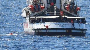 """مهاجر يقفز من سفينة """"أوبن آرمز"""" قبالة ساحل جزيرة لامبيدوزا الإيطالية."""
