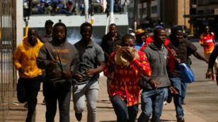 Manifestantes escapan del gas lacrimógeno lanzado por la policía en una protesta el 16 de agosto de 2019 en Harare.