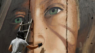 فنان الشارع الإيطالي جوريت أغوش يرسم جدارية عهد التميمي على الجدار الفاصل في الضفة.