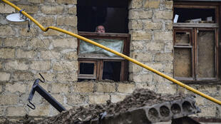 An elderly man looks out from a building damaged by an explosion in the breakaway Nagorno-Karabakh region's main city of Stepanakert