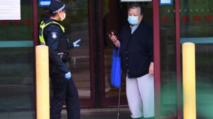 شرطية تتحدث إلى أحد القاطنين في برج سكني فرضت عليه إجراءات إغلاق، في ملبورن في 6 تموز/يوليو 2020