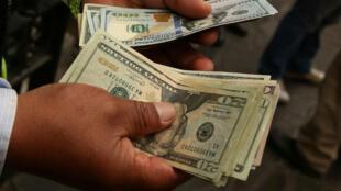 Un cambiador de dinero tiene billetes de un dólar en una calle del centro de Lima. Archivo.