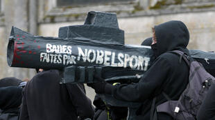 """Une manifestante tient une fausse arme à feu sur laquelle est écrit """"Balles faites par Nobel Sport"""", le 23 octobre 2015 à Pont-de-Buis-les-Quimerch."""