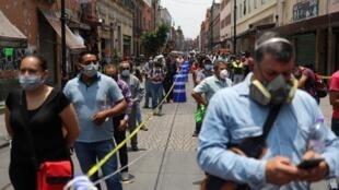 Decenas de personas hacen fila en la calle, para entrar al área donde están las tiendas, en medio de la reapertura económica gradual autorizada por el Gobierno de Andrés Manuel López Obrador, en Ciudad de México, México, el 6 de julio de 2020.