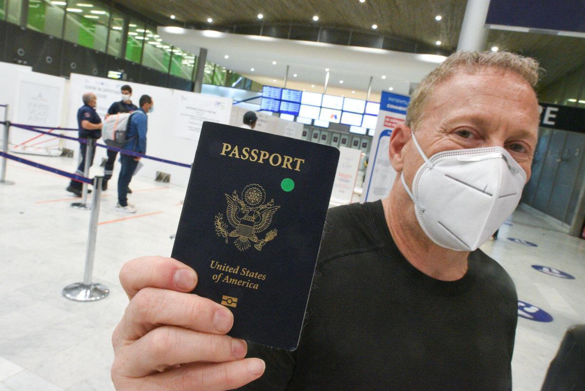 Rob, un Américain originaire de Californie du Nord, montre le petit autocollant vert sur son passeport. Cela signifie qu'il a fait un test Covid avant d'embarquer pour la France. Photo prise à à l'aéroport Roissy-Charles-de-Gaulles le 04 août 2020