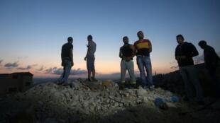 فلسطينيون يقفون على ركام منزل هدمته القوات الإسرائيلية في جنين