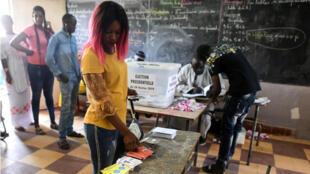 Una mujer se apresta a votar en las elecciones presidenciales en un puesto de votación en el barrio Medina de Dakar, el 24 de febrero de 2019