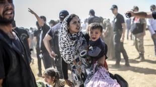 Une Kurde syrienne traverse la frontière entre la Syrie et la Turquie, le 23 septembre 2014.