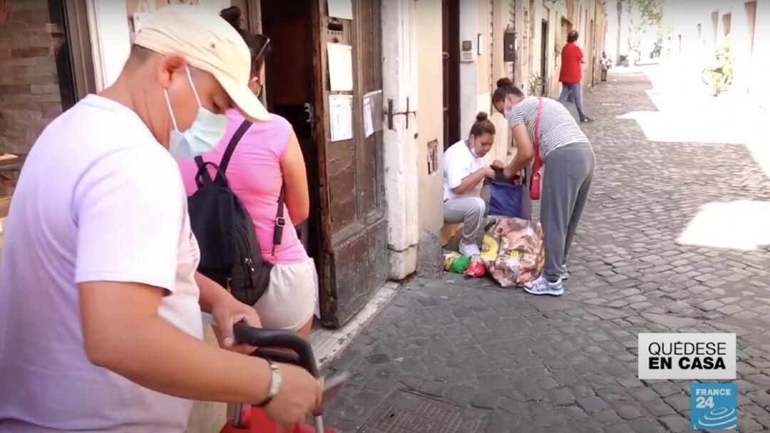 Una migrante peruana recibe ayuda alimentaria en medio de la pandemia ante una iglesia en Roma, Italia.