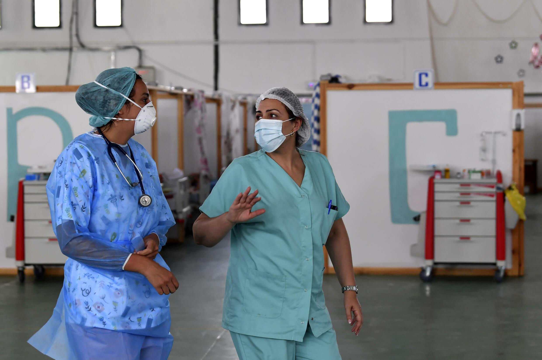 Des médecins tunisiens s'occupent de patients dans un gymnase qui a été aménagé pour faire face à la recrudescence des nouvelles infections au Covid-19 dans la ville de Kairouan, dans le centre-est du pays, le 4 juillet 2021
