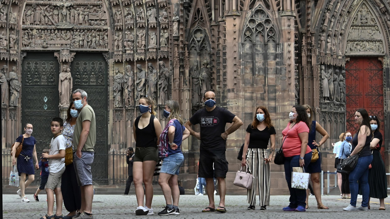 Varios ciudadanos con mascarillas de protección hacen una fila ante una heladería en Estrasburgo, Francia.