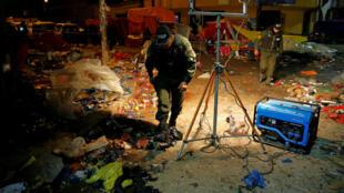 Oficiales de policía inspeccionan el sitio de la explosión de una botella de gas de cocina durante el desfile de Carnaval en Oruro.