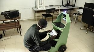 """Lamine Mouhamed Kébé, a final-year mechanical engineering student at the Ecole Supérieure Polytechnique in Dakar, Senegal, and coordinator of the """"Dr. Car"""" project, handles a small robot in the school's lab on May 8, 2020."""