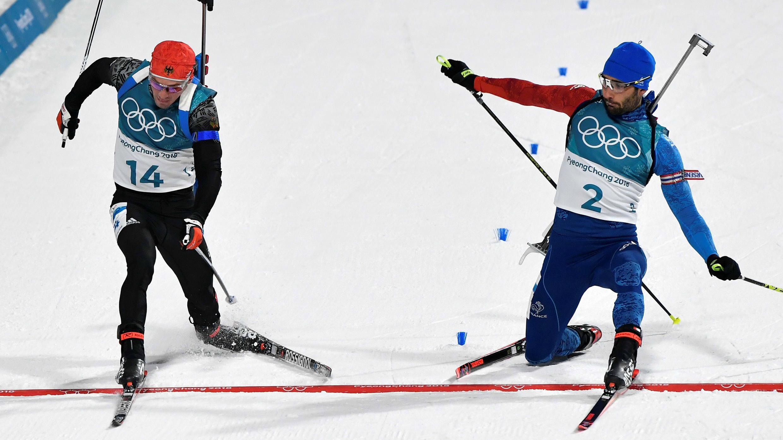 El francés Martin Fourcade aventaja por milímetros al alemán Simon Schempp en la definición de los 15 kilómetros de salida en masa de biatlón en Pyeongchang, el 18 de febrero de 2018.