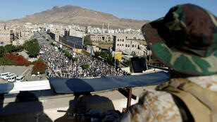 Un rebelde hutí hace guardia mientras otros militantes protestan en Saná, Yemen, por la devaluación del rial yemení el 5 de octubre de 2018.