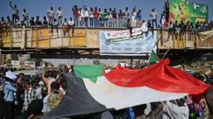Los manifestantes sudaneses ondean la bandera de su país durante la 'marcha del millón' frente al cuartel general del Ejército en la capital, Jartum, Sudán, el 25 de abril de 2019.