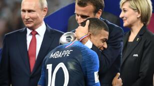 Emmanuel Macron félicite Kylian Mbappé, en présence de Vladimir Poutine, au stade Luzhniki, à Moscou, le 15 juillet 2018.