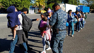 Caravana de migrantes de El Salvador forman una línea en un punto fronterizo en ruta a los Estados Unidos, en Pedro de Alvarado, el 16 de enero de 2019.