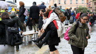 Tourists wade through water during high tide in Venice, Italy, on November 17, 2019.