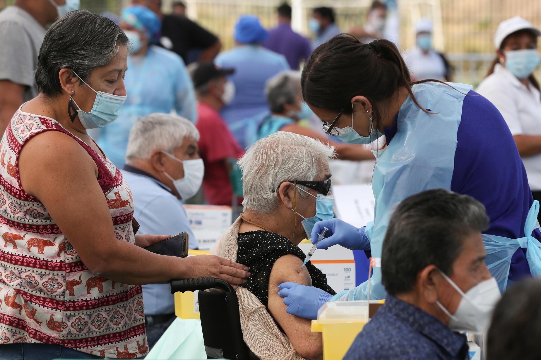 Una trabajadora de la salud administra una dosis de la vacuna CoronaVac de Sinovac contra el coronavirus a una mujer en un centro de vacunación en Santiago, Chile , el 3 de febrero de 2021.