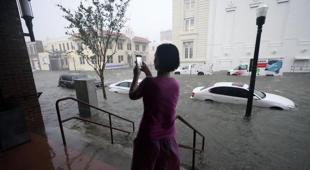 Una mujer toma fotografías de vehículos en una calle inundada, tras la llegada del huracán Sally, en Pensacola, Florida, el 16 de septiembre de 2020.