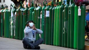 Alejandro Ccasa reza después de esperar tres días junto a un tanque de oxígeno vacío por su tío que tiene Covid-19. Fotografía tomada en Callao, Perú, el 2 de febrero de 2021.